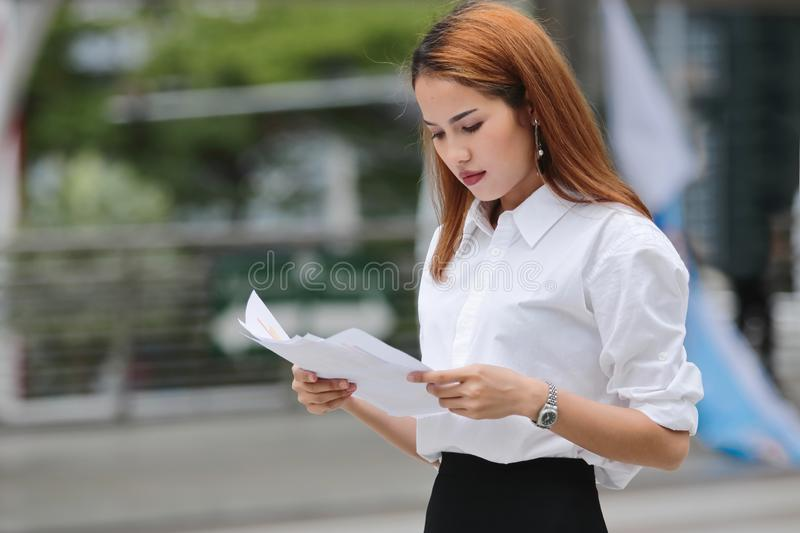 Confident young Asian business woman holding and analyzing paper charts on hands stock photo