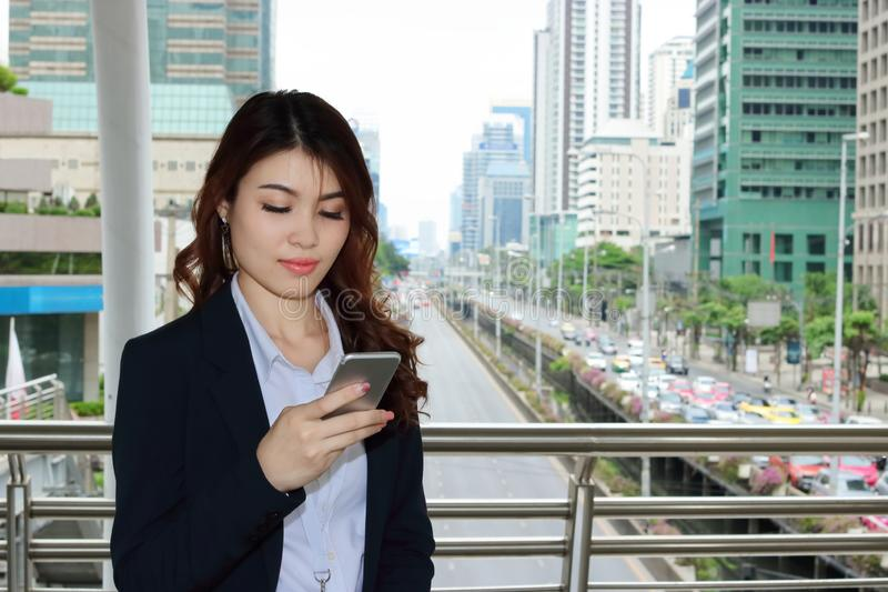 Confident young Asian business woman looking mobile smart phone in her hands at urban building city background. stock photography