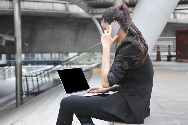 Confident young Asian business woman using laptop and mobile smart phone for job at outside office.  stock image