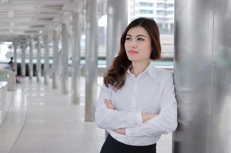 Confident young Asian busineswoman leaning a pole at walkway outside office. Leader business woman concept. Confident young Asian busineswoman leaning a pole at stock image