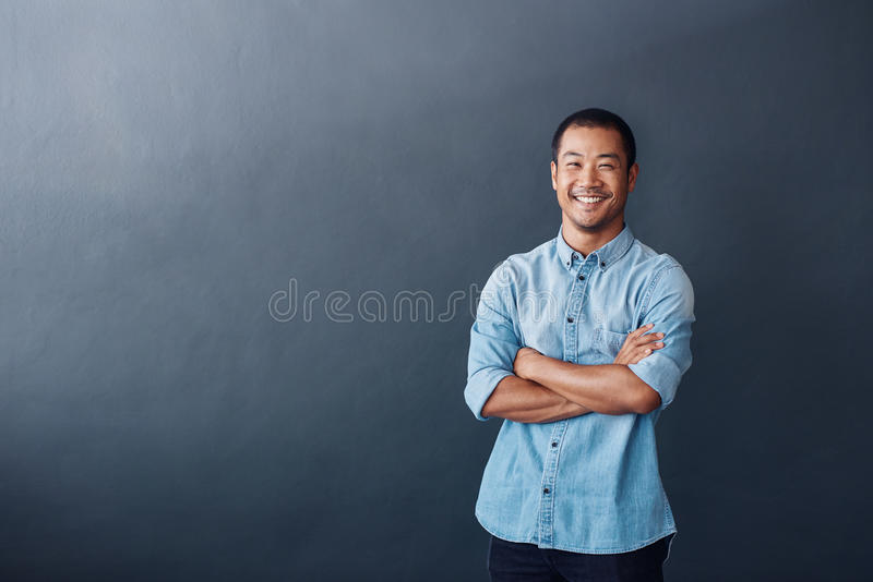 Confident young Asian designer standing in a modern office stock image