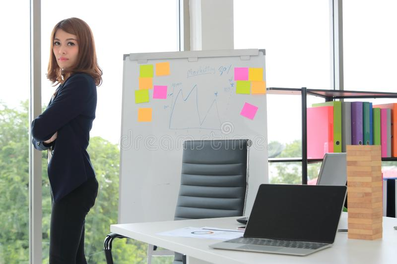 Confident young Asian executive woman standing in office. Thoughtful and leadership business concept stock image
