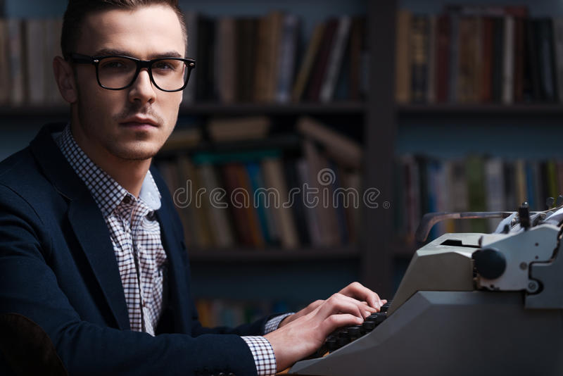 Confident young author. Side view of confident young author sitting at the typewriter and looking at camera with bookshelf in the background royalty free stock photography