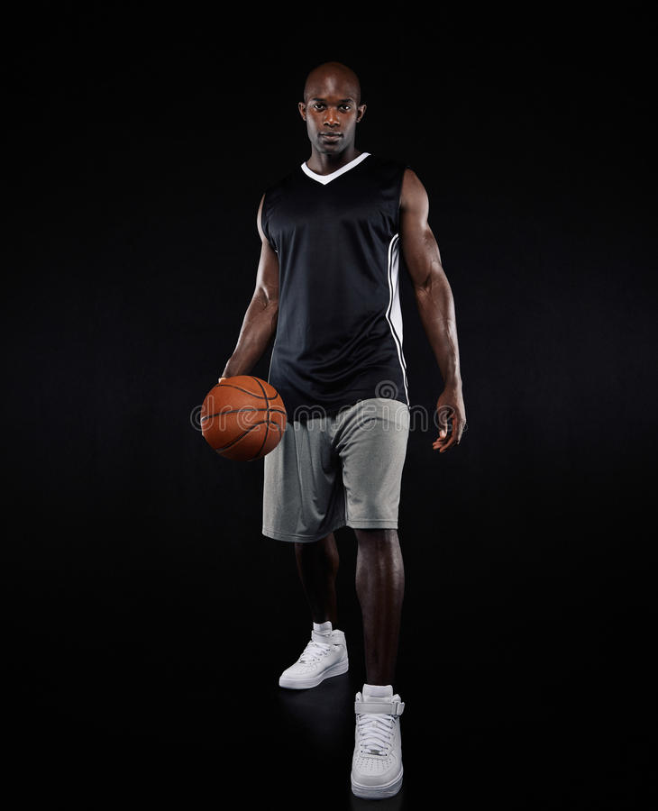 Confident young basketball player over black background royalty free stock image