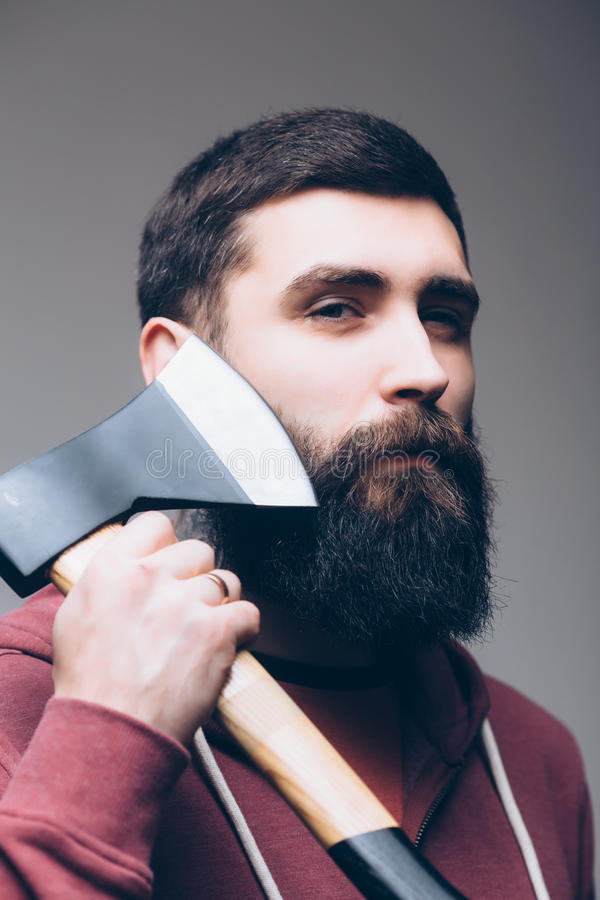 Confident young bearded man carrying a big axe royalty free stock photos