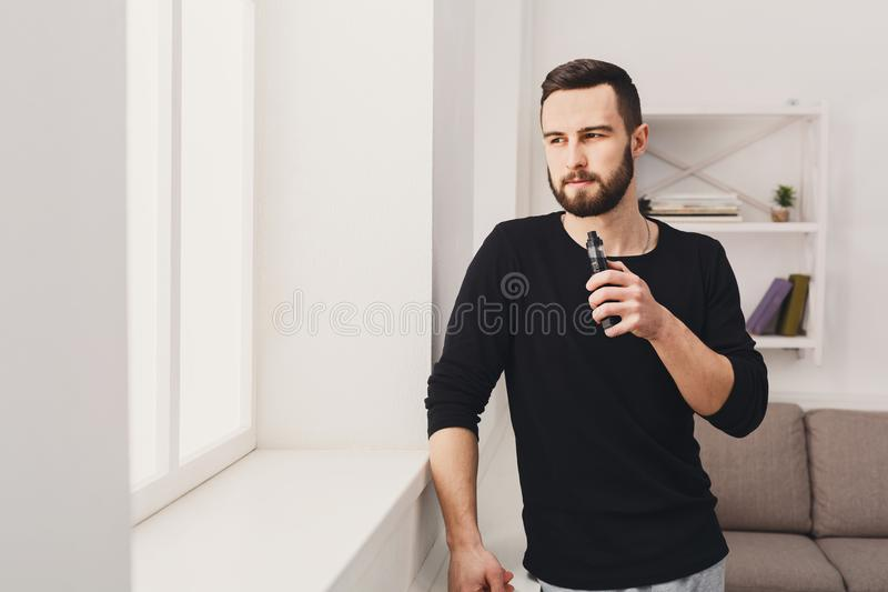 Young man vaping e-cigarette on white. Confident young bearded man vaping electronic cigarette standing against the window on white background. Nicotine free stock photo