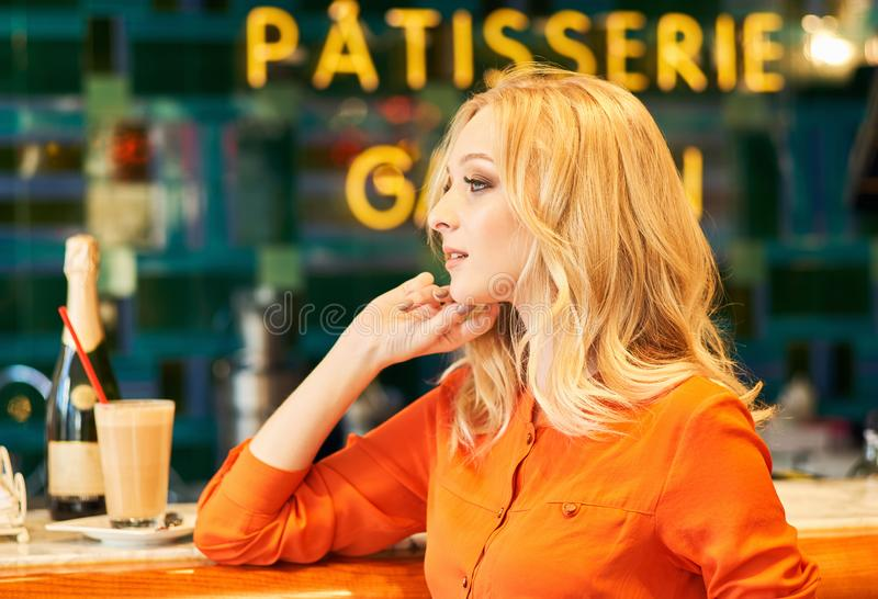Confident young blonde lady sitting at bar in cafe stock photos