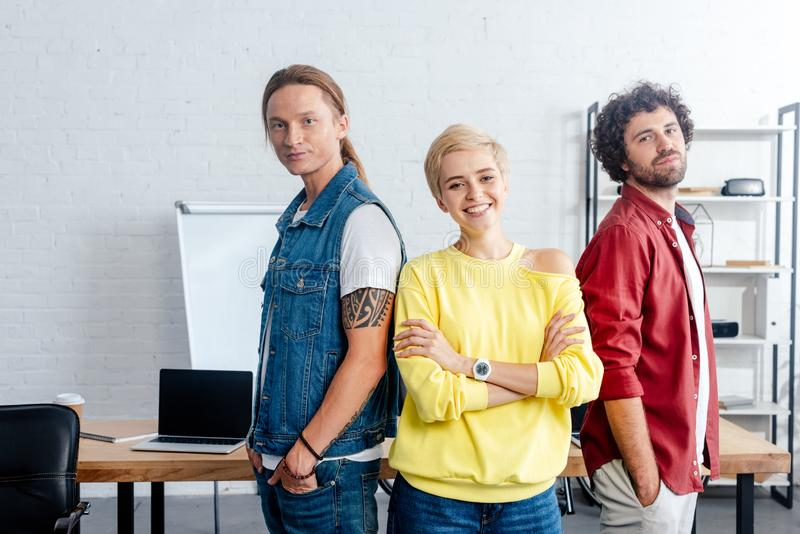 confident young business people standing together and smiling at camera royalty free stock photo