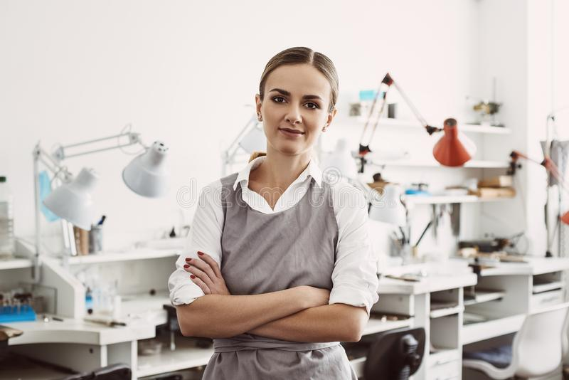 Confident and young business woman. Portrait of smiling female jeweler in apron standing at her jewelry workshop stock image