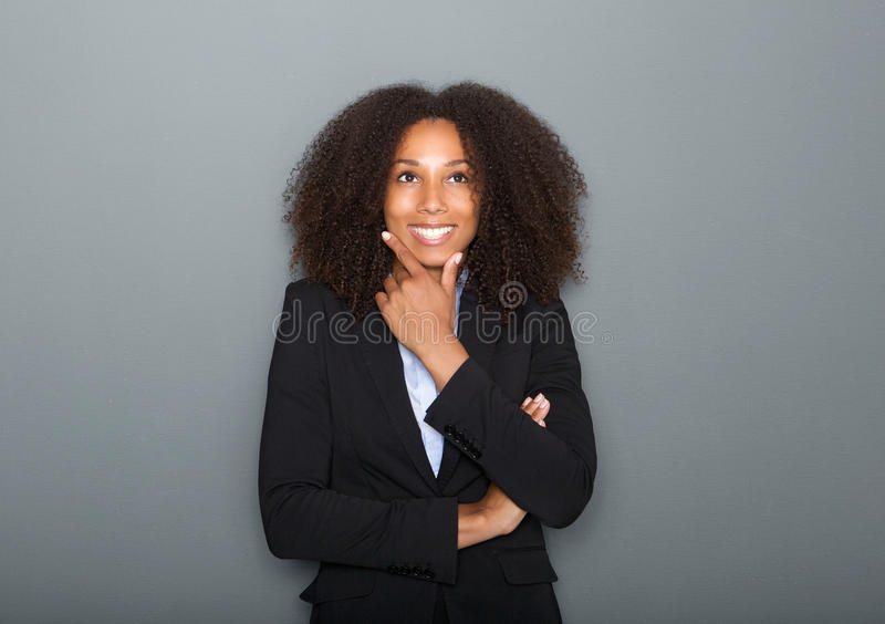 Confident young business woman thinking on gray background royalty free stock images