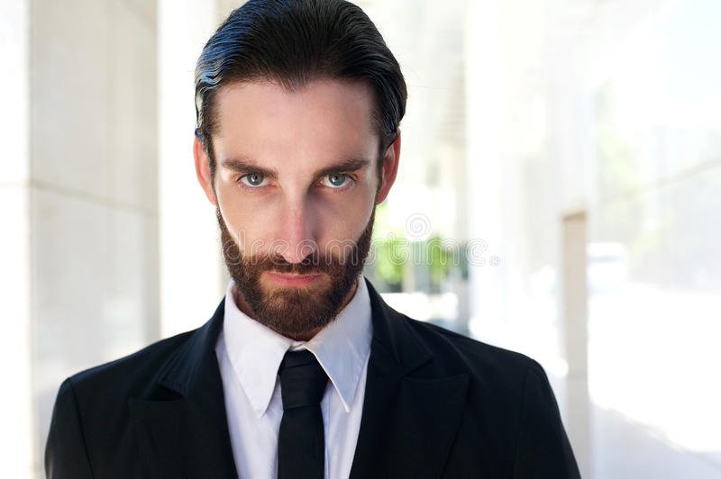 Confident young businessman with beard in black suit and tie stock photography