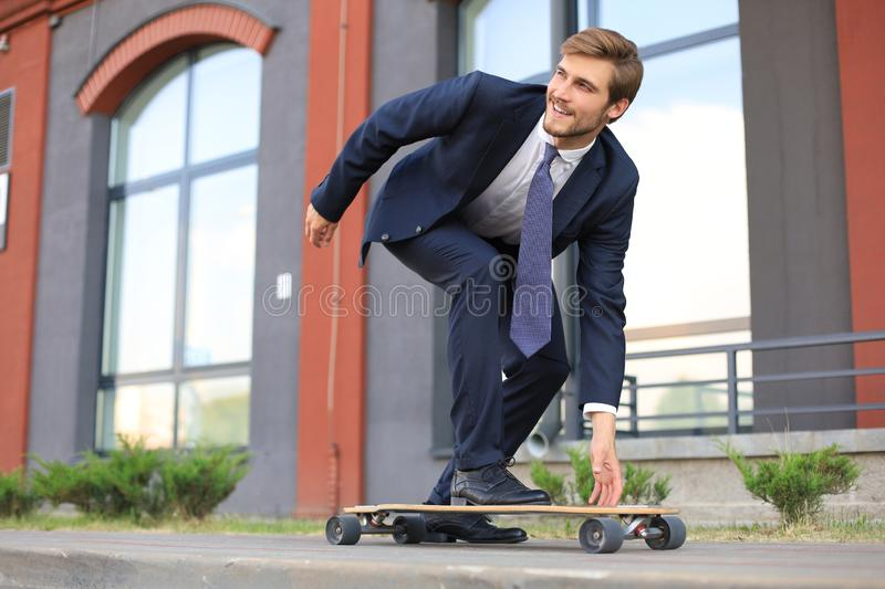 Confident young businessman in business suit on longboard hurrying to his office, on the street in the city. stock images