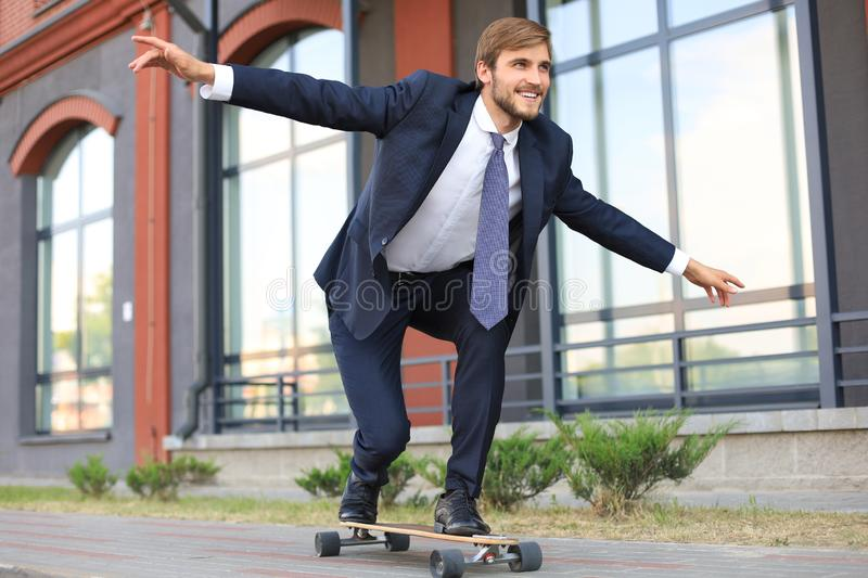 Confident young businessman in business suit on longboard hurrying to his office, on the street in the city. royalty free stock image