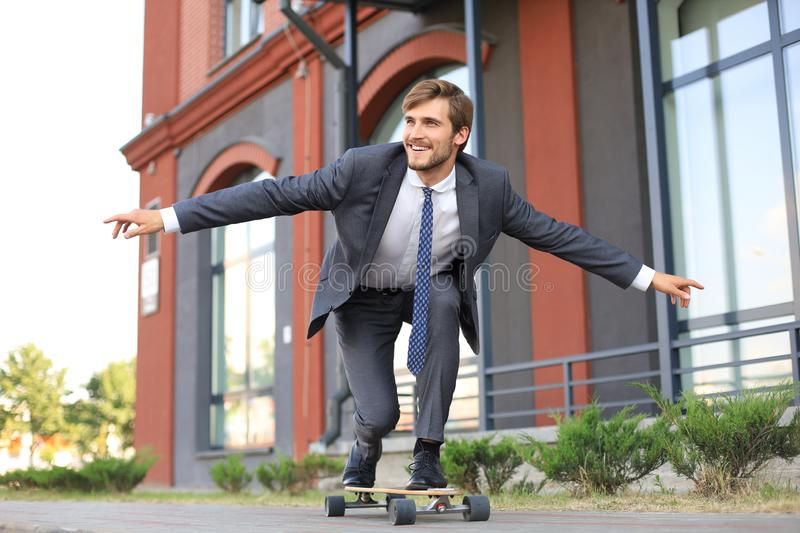 Confident young businessman in business suit on longboard hurrying to his office, on the street in the city. stock photo