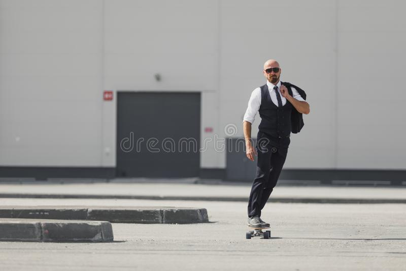 Confident young businessman in business suit on longboard hurrying to his office, on the street in the city stock photography
