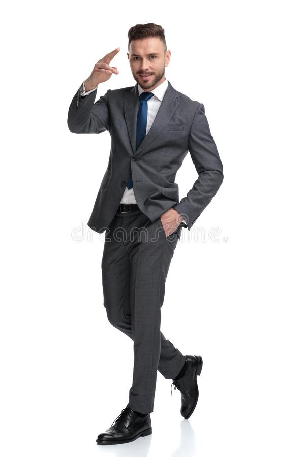 Confident young businessman giving a military salute while walking stock image