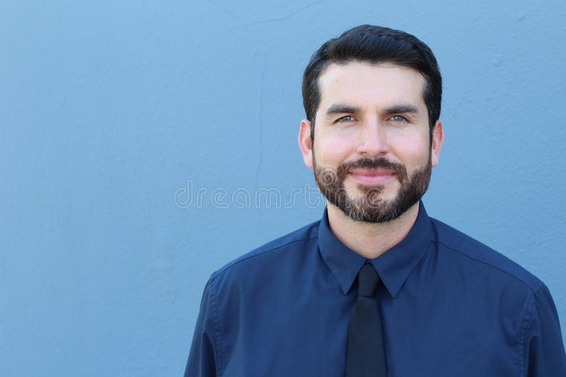 Confident young businessman smiling on blue background with space for copy.  royalty free stock photo