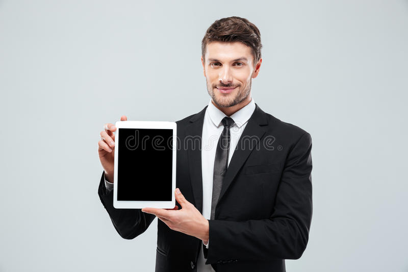 Confident young businessman standing and showing blank screen tablet. Over white background royalty free stock photo