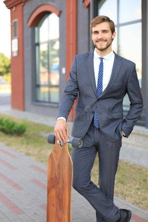 Confident young businessman walking on the street, using longboard. stock image