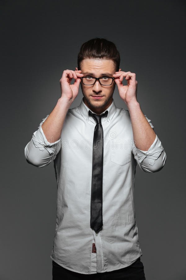 Confident young businessman in white shirt, tie and glasses royalty free stock photo