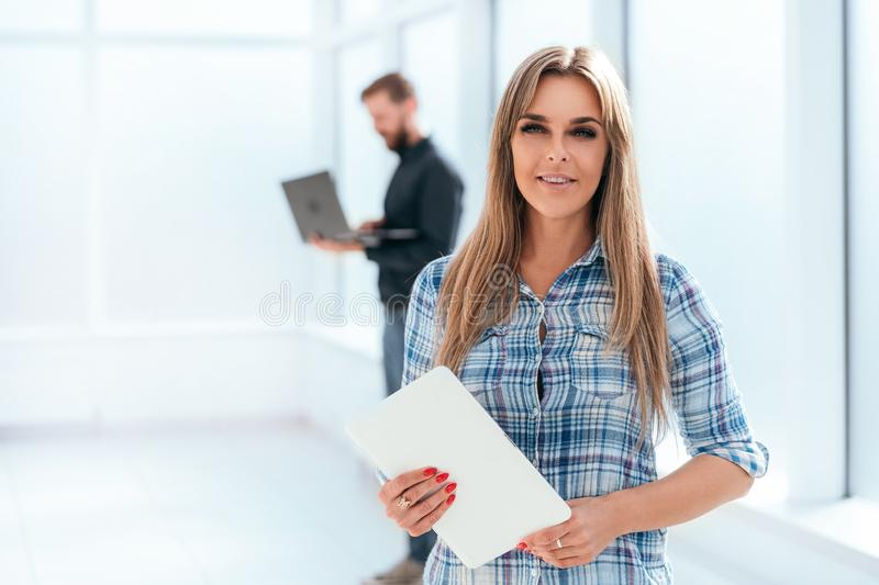 Confident young businesswoman with digital tablet standing in a new office stock image