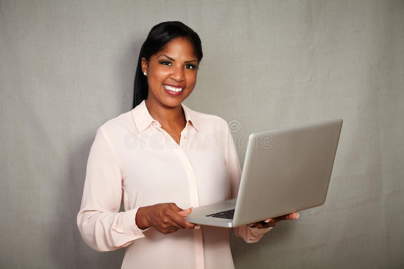 Confident young businesswoman holding a laptop royalty free stock photo