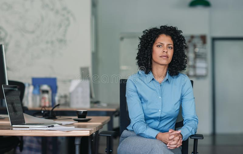 Confident young businesswoman sitting at her desk in an office royalty free stock images
