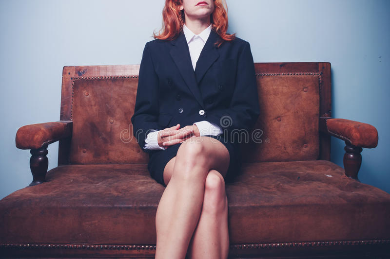Confident young businesswoman sitting on sofa stock images