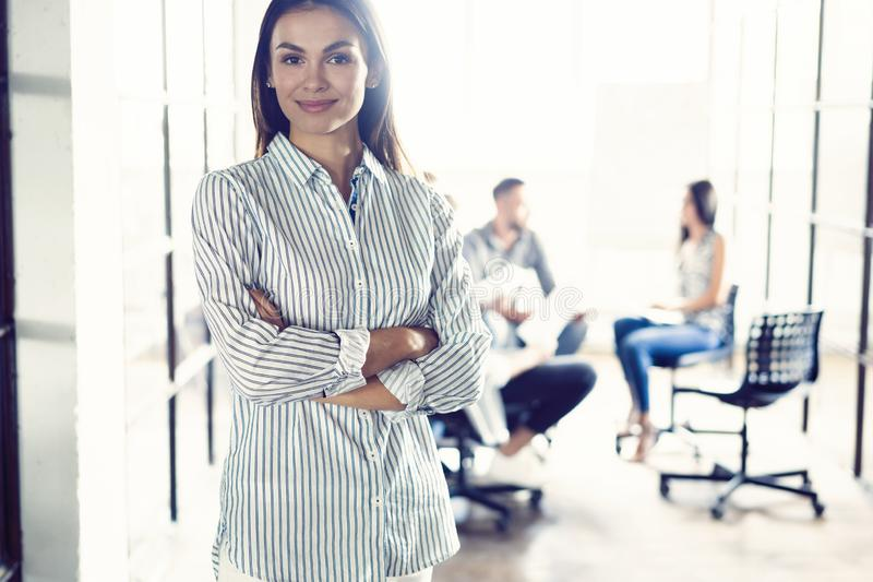 Confident young businesswoman standing with her arms crossed in a modern office with colleagues working in the stock photos