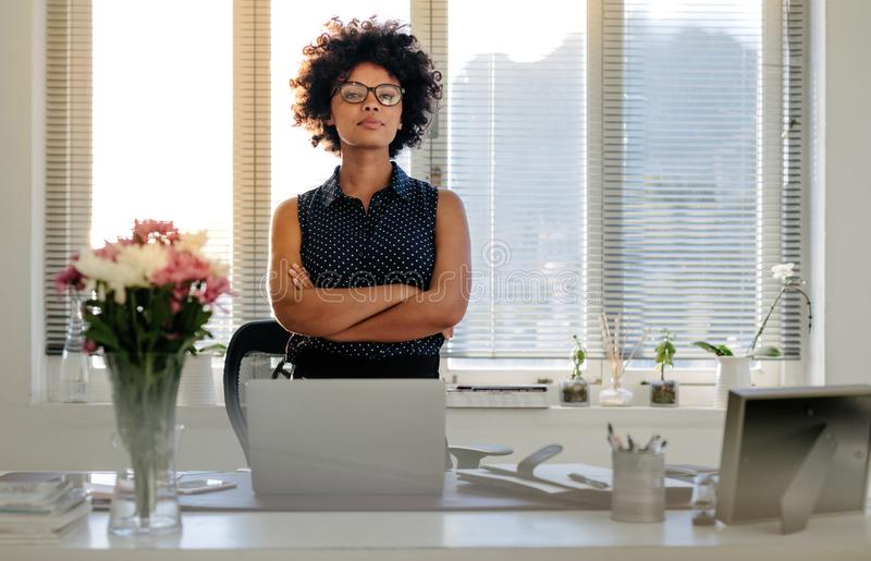Confident young businesswoman standing at her desk stock photography