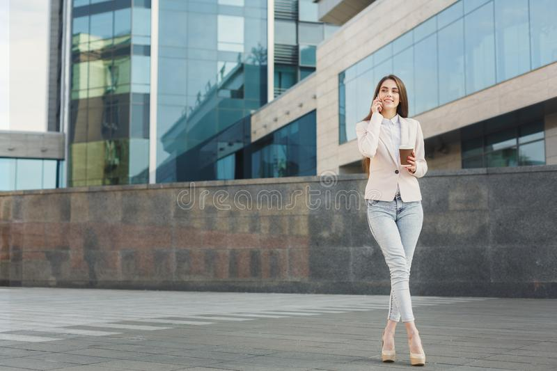 Confident young businesswoman talking on mobile. Confident businesswoman talking on smartphone outdoors. Young xecutive having conversation, drinking take away stock images