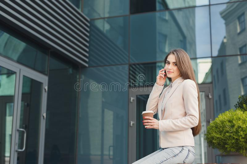 Confident young businesswoman talking on mobile. Confident businesswoman talking on smartphone outdoors. Young xecutive having conversation, drinking take away royalty free stock images