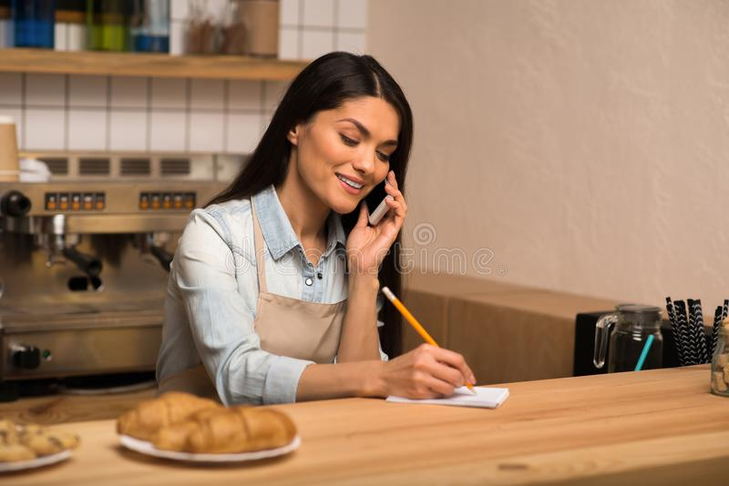 Cafe owner taking notes. Confident young cafe owner taking notes and talking on smartphone royalty free stock photo