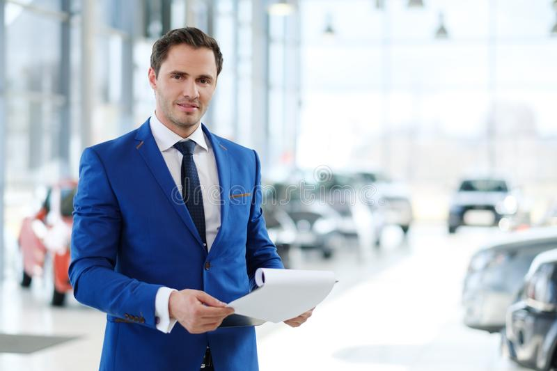 Confident young car dealer standing in showroom. royalty free stock photography