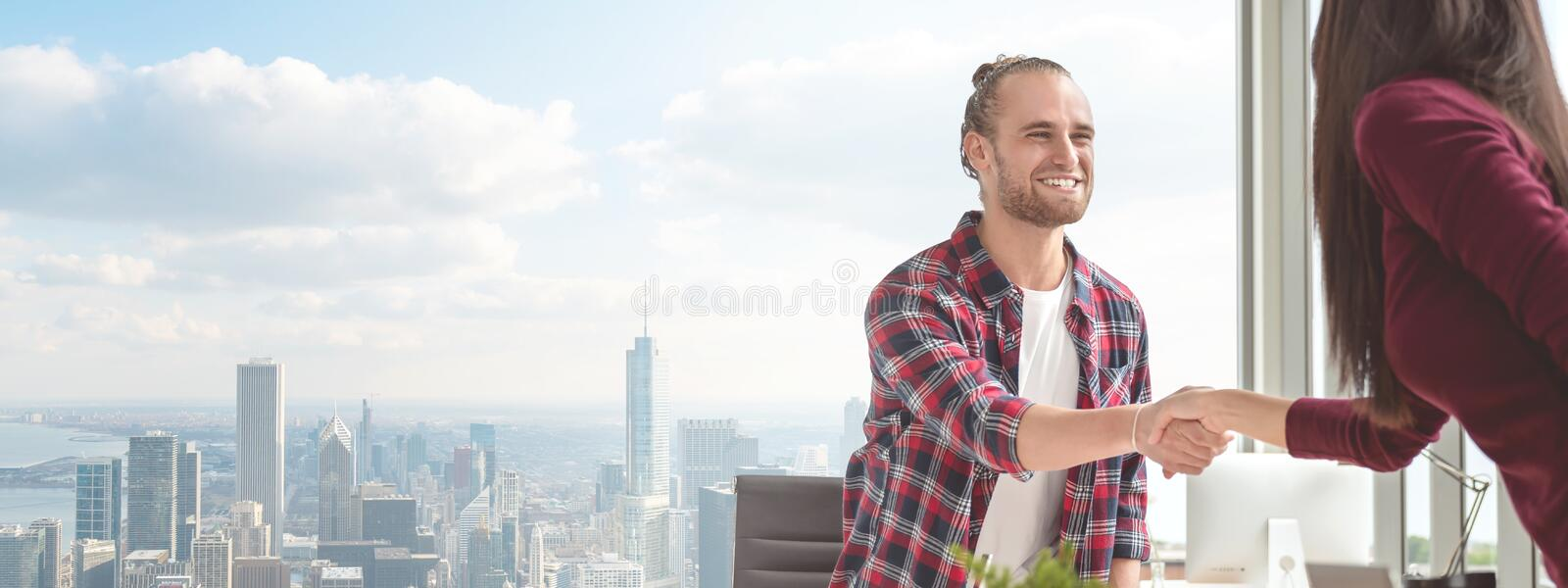Confident young caucasian asian man shaking hands with partner woman in business agreement smiling together feeling happy. Banner stock photo
