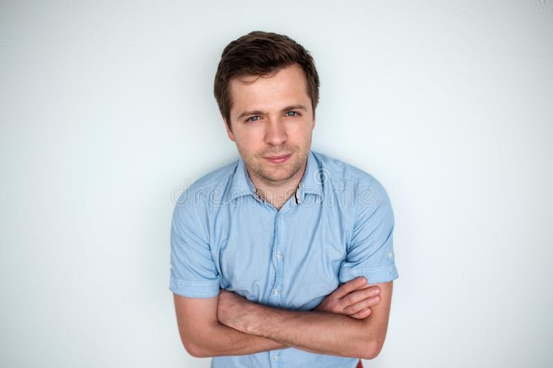 Confident young caucasian handsome man in blue shirt keeping arms crossed and smiling royalty free stock image