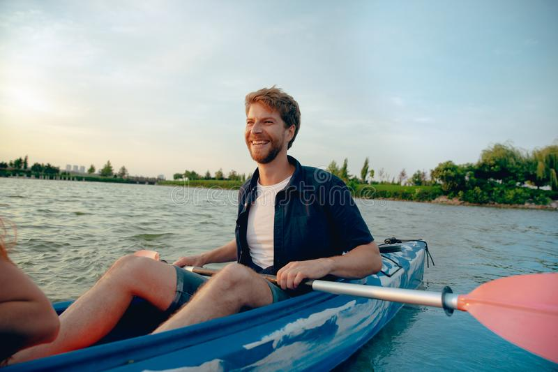 Confident young man kayaking on river with sunset on the background. Confident young caucasian man kayaking on river with sunset in the backgrounds. Having fun stock photo