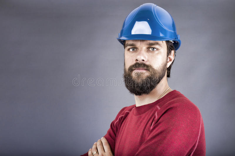 Confident young construction worker with hardhat and arms folded royalty free stock photos