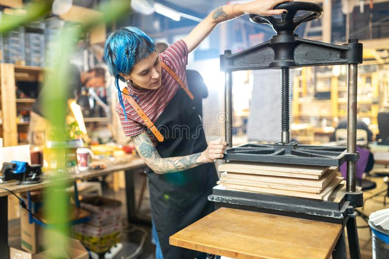 Young woman doing woodwork in a workshop royalty free stock photo