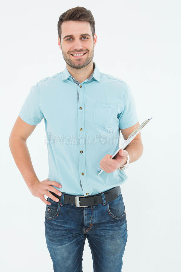 Confident young delivery man holding clipboard. Portrait of confident young delivery man holding clipboard on white background stock images