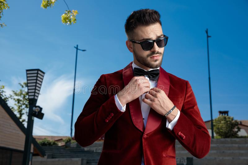 Confident young elegant man arranging shirt outside royalty free stock images