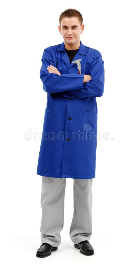 Confident young engineer with folded arms. Confident young engineer standing with arms folded and looking. Caliper on his upper pocket royalty free stock photo