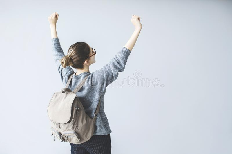 Confident young female student raised up arms with backpack royalty free stock photos