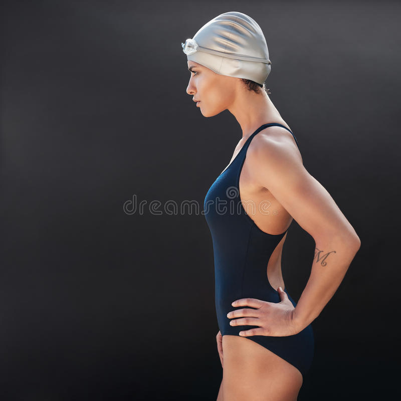 Confident young female swimmer. Side portrait of confident young female swimmer on black background. Young woman in swimsuit standing with her hands on hips royalty free stock photography