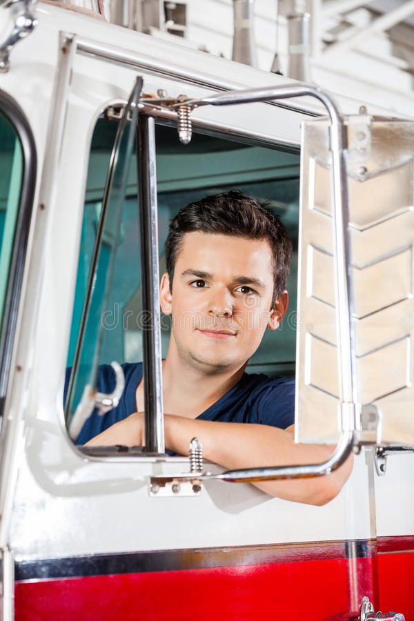 Confident Young Fireman Sitting In Firetruck royalty free stock images