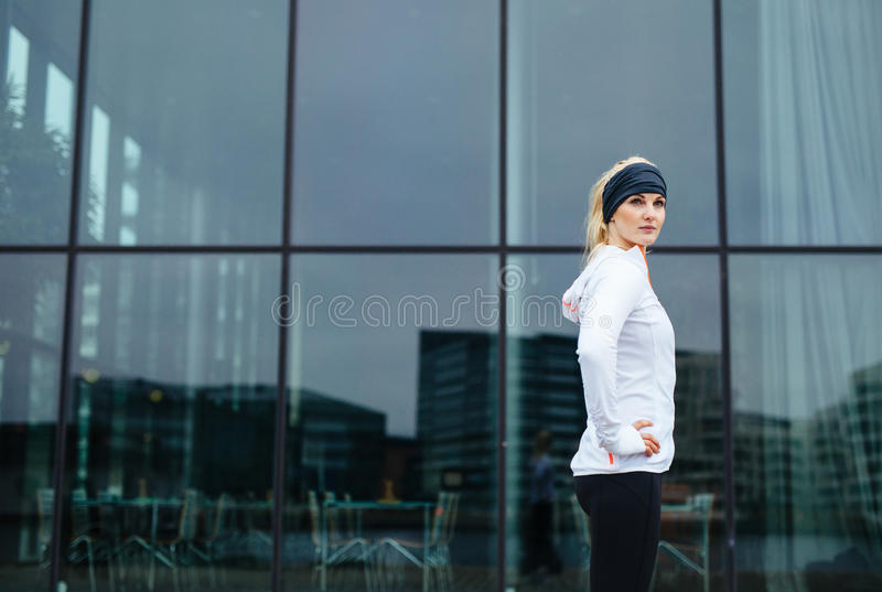 Confident young fitness woman. Portrait of confident young woman standing with her hands on hips looking at camera. Fitness model outdoors royalty free stock image