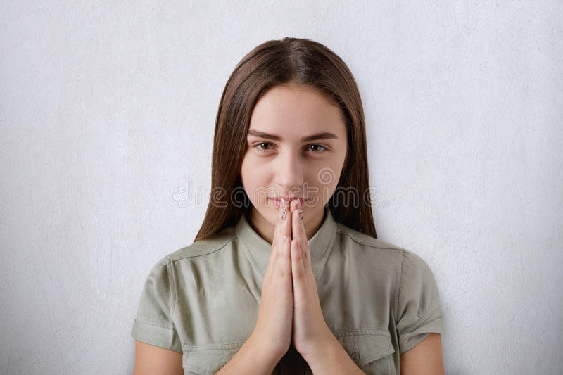 A confident young girl with beautiful dark eyes and hair praying with her hands together on grey background having believe in bett royalty free stock images