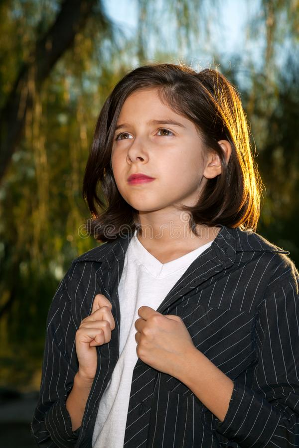 Confident Young Girl Looking Off in the Distance. A serious looking young girl holds the lapels of her outer shirt and looks solemnly off into the distance. Her royalty free stock photography