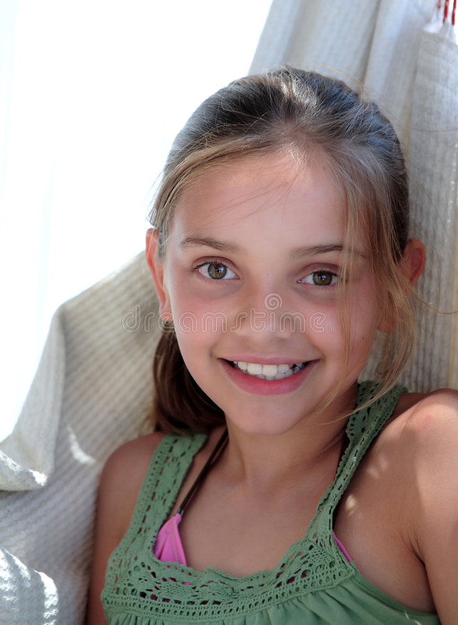 Confident young girl sitting in hammock on vacation stock photos