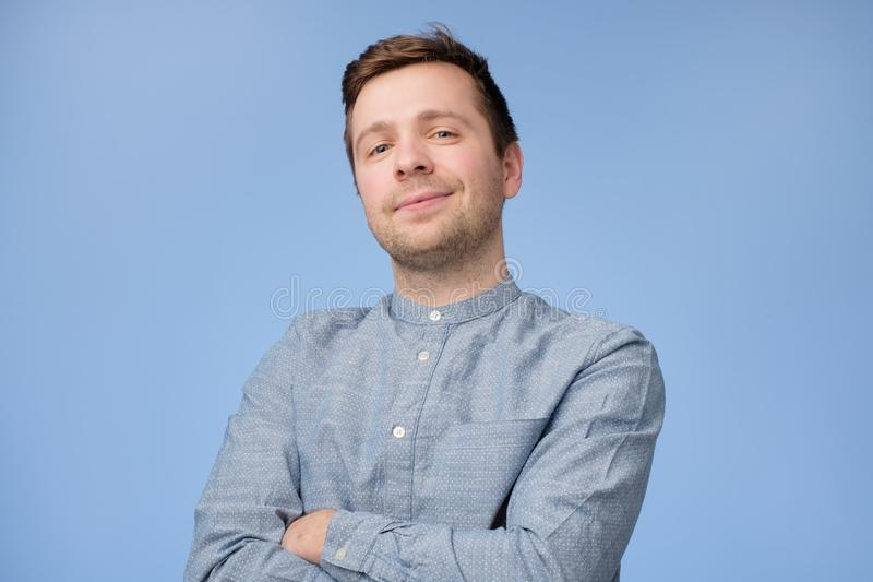 Confident young handsome man in blue shirt keeping arms crossed and smiling royalty free stock photos